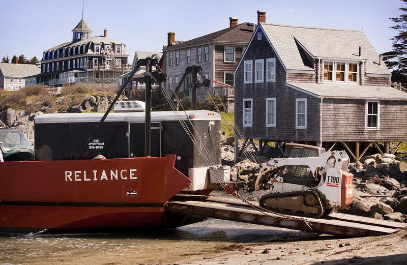 Contractors and equipment arrive on Monhegan, via landing vehicle, to take part in an Island Institute program to make Maine island homes more energy efficient. The workers eliminated air leaks in island homes by caulking cracks, installing weatherstripping and applying spray insulation.