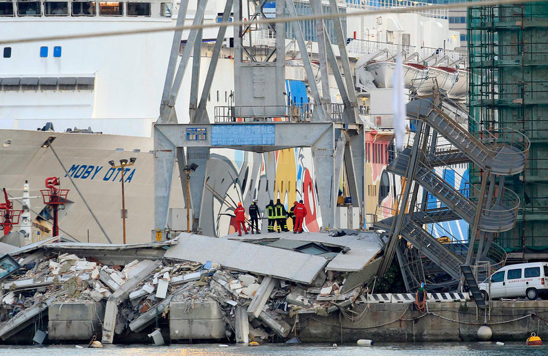 Rescue personnel stand in the wreckage of the control tower in the port of Genoa, Italy. At least seven were killed when the 40-ton ship slammed into the tower and dock.