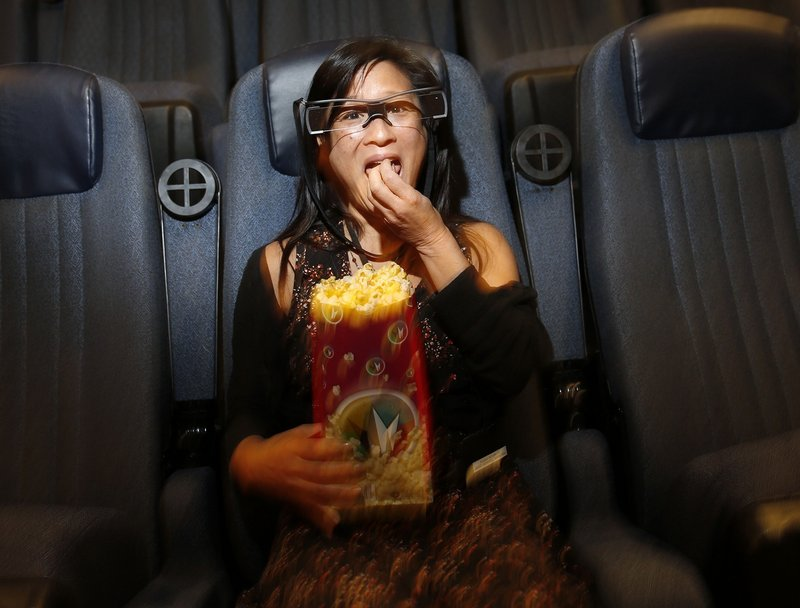 Lisa Yuan, who is hearing impaired, wears glasses that show captions at a Regal theater in Los Angeles.