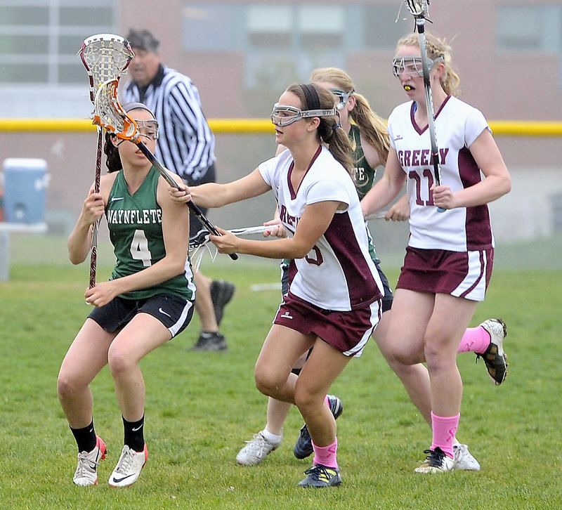 Sofia Canning of Waynflete looks to pass as Eliza McKenney, center, and Meg Finlay of Greely move in to defend.