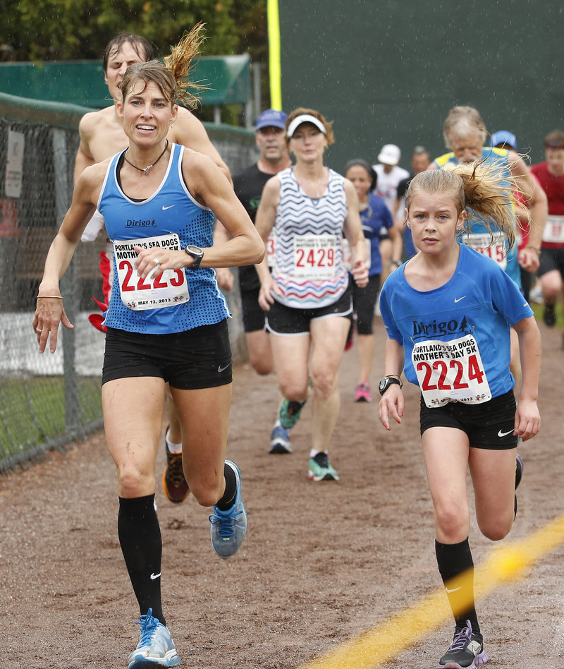 The mother and daughter team of Sheri and Karley Piers nears the finish line, daughter first, who ran best among the 14-and-under girls, finishing in 23:48, a few strides ahead of her mom.