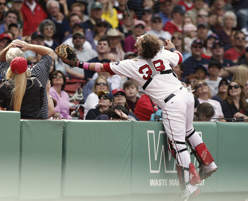 It's a stretch for Boston catcher Jarrod Saltalamacchia as he unsuccessfully reaches into the stands for a foul popup that lands some rows beyond his glove during the fourth inning of Sunday's loss to the Toronto Blue Jays at Fenway Park.