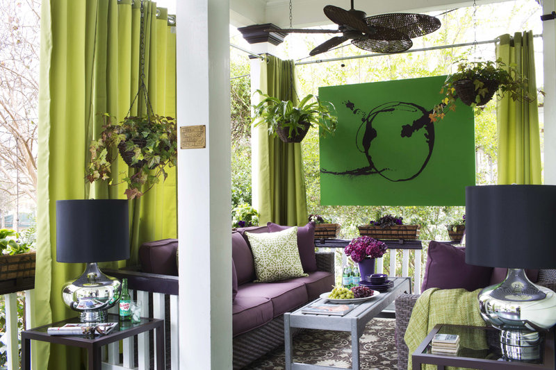 Drapery panels are added to this small Flynn-designed outdoor porch to emphasize the house's tall ceiling, minimize its narrow dimensions and give the space privacy. Another trick is to hang oversized art and flank seating areas with two love seats or sofas rather than chairs.