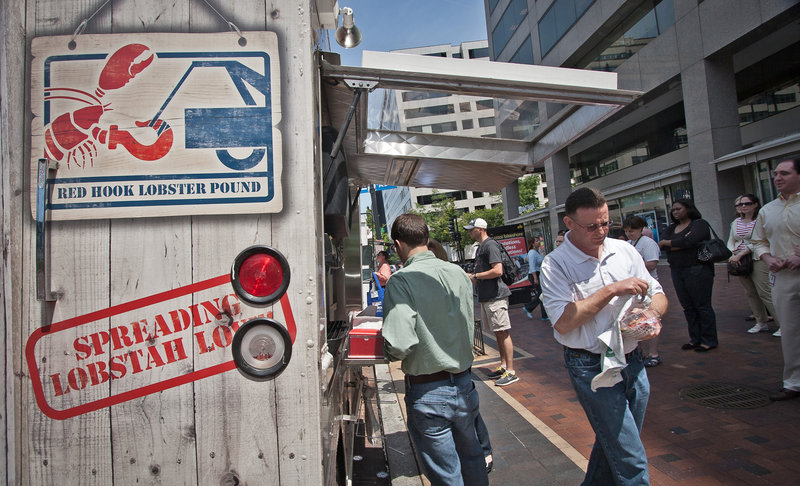 A customer leaves with lunch as dozens of others line up to purchase their own at The Red Hook Lobster Pound DC food truck in Washington D.C.