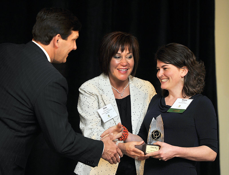 Masey Kaplan, right, receives the 2013 innovation award for her family business, Close Buy Catalog. Giving the award is emcee Gregg Lagerquist, a WGME-TV news anchor, and Gina Weathersby, executive director of the Institute for Family-Owned Business.