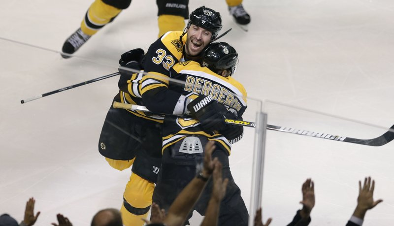 Zdeno Chara (33) leaps into Patrice Bergeron's arms after Bergeron scored the game-winning goal in Game 7 of the first round of the NHL Stanley Cup Playoffs on Monday night for the Boston Bruins.