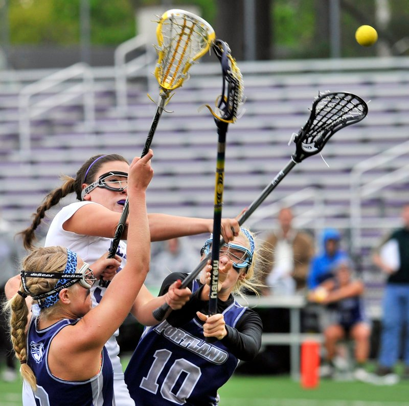 Julianna Salamone of Deering fires a shot between two Portland defenders – Hallie Alex, left, and Cole Spike – in a Class A lacrosse game at Deering's Memorial Field. Portland won, 13-5.