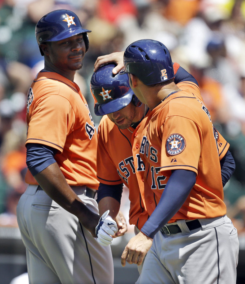 J.D. Martinez, center, is congratulated by Houston teammates Chris Carter, left, and Carlos Pena after his home run gave the Astros a 5-4 lead in a rare win over Detroit.