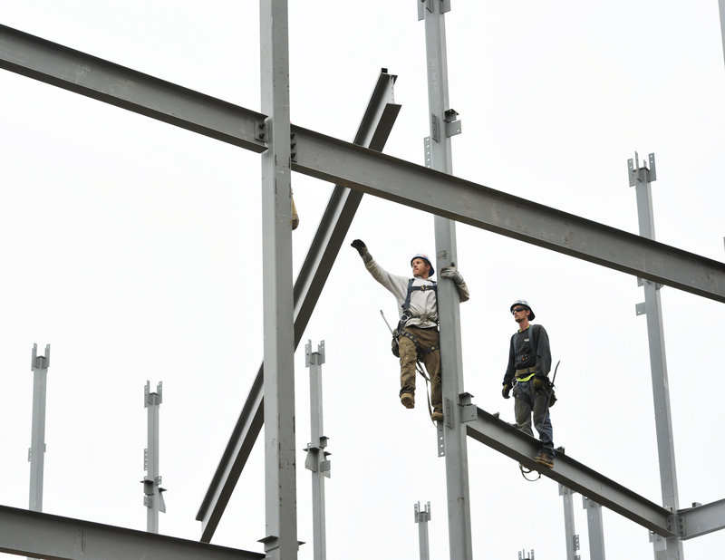 Steel workers position beams Tuesday at the construction site for a new Marriott hotel on Commercial Street in Portland. Despite a spate of new hotel projects in Portland and a 2012 surge in home construction in southern Maine, many areas of the state still are struggling to recover from the effects of a real estate slump in 2009.