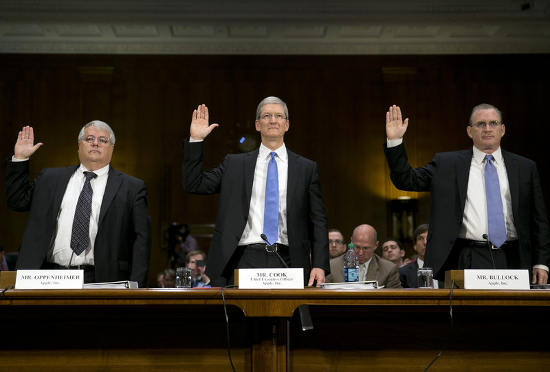 Apple executives are sworn in at Tuesday's Senate hearing. From left are Peter Oppenheimer, senior vice president and chief financial officer; Tim Cook, chief executive officer; and Phillip Bullock, head of tax operations.