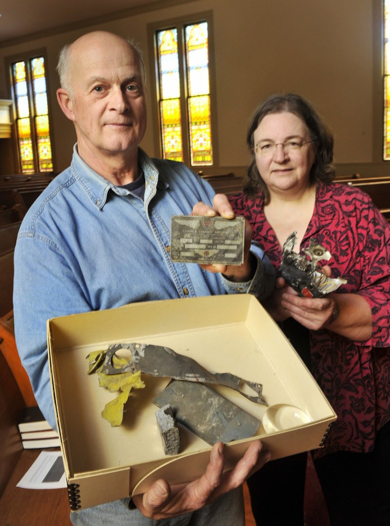 Phil Blake displays parts of a British fighter plane that were recovered after a midair crash over New Gloucester in 1943. He wants to add the pilots' names to the town's planned veterans monument. Town archivist Linda Gard, right, helped Blake research the incident.