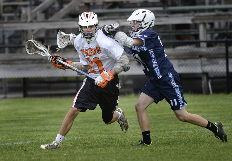 Chad Pelletier of Westbrook, right, applies the defense as Kyle Rhames of Biddeford looks for an opening on offense during their lacrosse game.