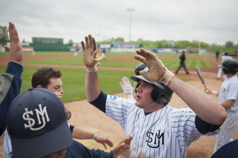 Chris Bernard gets a welcome reception in the Southern Maine dugout after scoring in the sixth inning Monday.