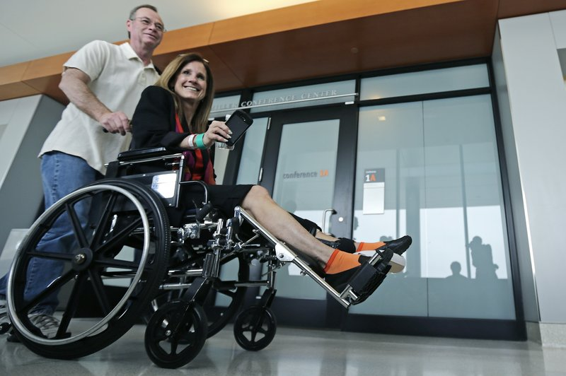 Boston Marathon explosion survivor Beth Roche, of Highland, Ind., is pushed through the hallway at the Spaulding Rehabilitation Hospital by her husband Ken Roche, in Boston, Tuesday, May 28, 2013. Roche said she is hoping to meet a man who helped her at the bombing scene, who she has yet to find, before her hospital discharge later this week. (AP Photo/Charles Krupa)