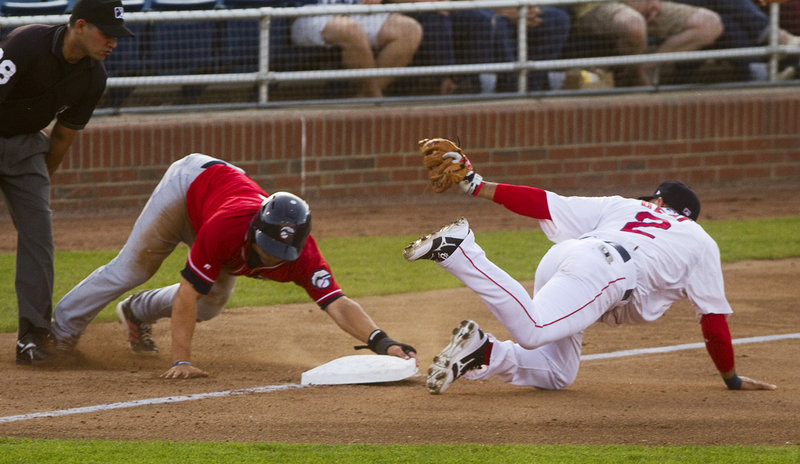 Portland third baseman Ryan Dent gets the throw late as New Hampshire baserunner Kevin Pillar advances safely during Thursday's game in Portland, won by the Fisher Cats.