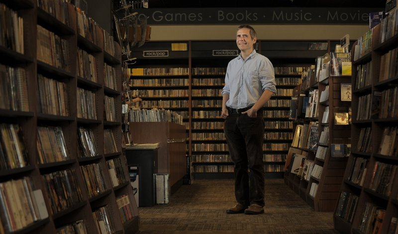 "Bull Moose founder and sole owner Brett Wickard, shown in his South Portland store, says to compete with the big online book and music sellers, ""It's our job to listen to our customers and adapt and kind of roll with the punches."""