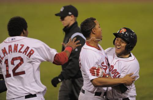 Heiker Meneses, right, is greeted by Xander Bogaerts as Michael Almanzar rushes in Wednesday night. Meneses singled in the winning run in the 10th inning as the Portland Sea Dogs defeated the New Hampshire Fisher Cats 5-4 at Hadlock Field.