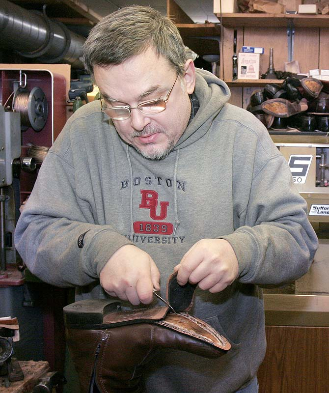 Charles Scontras replaces part of the sole of a boot while working in his shop, the Saco Shoe and Leather Hospital, in 2006. Scontras died in the fire after Saturday's standoff.