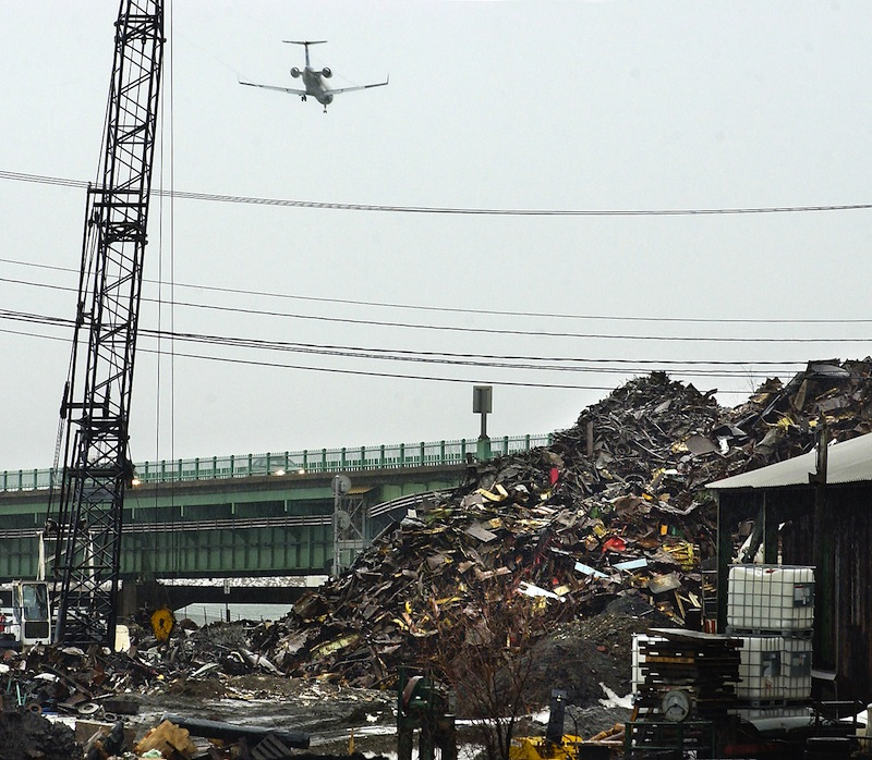 In this 2005 file photo, a jet flies over a scrap-metal yard between the Merrill Marine Terminal and the Veterans Bridge. One of many new Maine laws broadens the form of payment allowed by scrap-metal dealers for materials they buy to credit or debit cards. An earlier law allowed only checks.