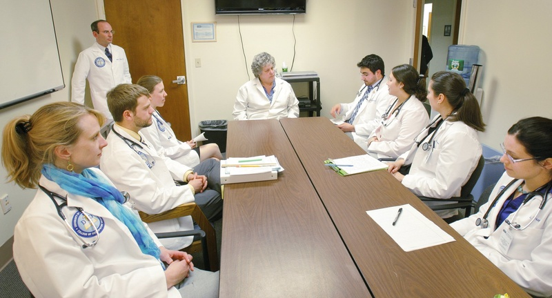 Elisabeth DelPrete, D.O., center, chair of the University of New England's department of family medicine, meets with medical students. Many of Maine's primary care doctors are UNE graduates.