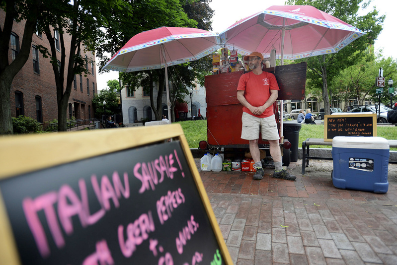 Mark Gatti is ready to serve customers at his Mark's Hot Dogs stand Monday. He and his father built the red food cart from which Gatti has sold more than 840,000 hot dogs.
