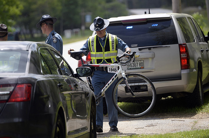 State police move a bike that was involved in a fatal crash in Hanover on Friday. David LeClair, a 23-year-old cyclist from Watertown, Mass., was struck by a tractor-trailer just miles from the starting point of the annual Trek Across Maine cycling event.