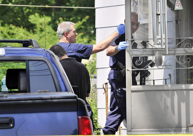 Maine State Police evidence technicians enter the home on Route 136 in Freeport where a father and son were found dead Tuesday.