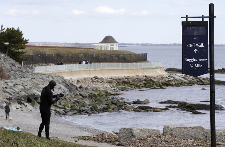 A surfer stands at the coast in Newport, R.I., in March. Scientists say tsunami-like conditions were recorded along part of the East Coast in June. The highest peak amplitude was recorded in Newport.
