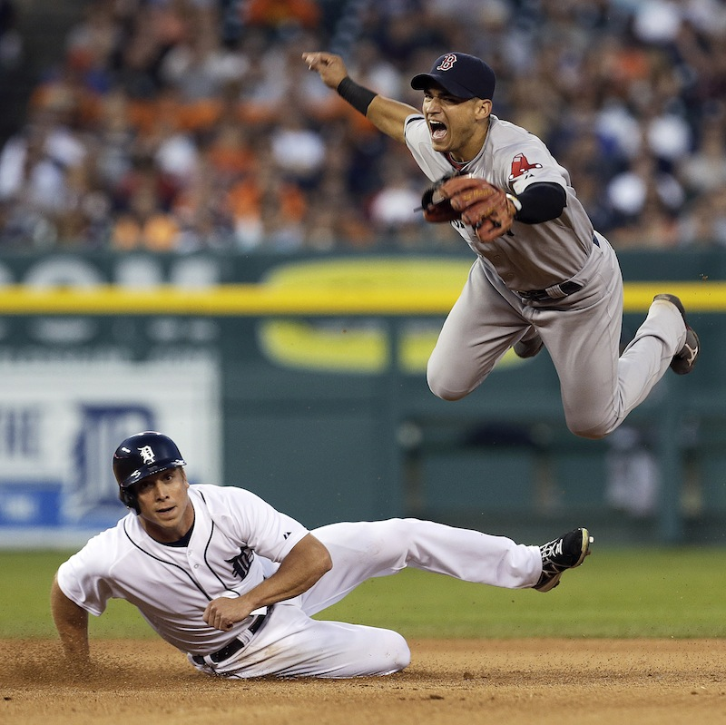 Boston Red Sox's Jose Iglesias jumps after Detroit Tigers' Andy Dirks slides to break up the throw to first base on a Brayan Pena fielder's choice in Detroit on Thursday. Pena was safe at first base.