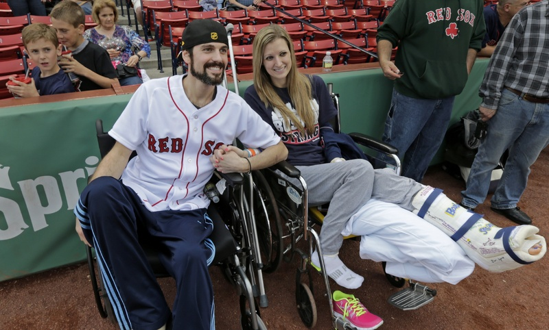Boston Marathon bombing survivor Pete DiMartino, of Rochester, N.Y., and his girlfriend, Rebekah Gregory, hold hands prior to DiMartino throwing out the ceremonial first pitch before a Red Sox game at Fenway Park in Boston last month. DiMartino is among those applying for compensation from The One Fund.