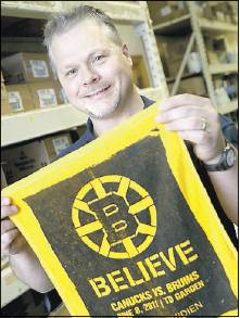 Boston Bruins fan Jim Joyce, right, who works at Maine Hardware in Portland, on Tuesday holds a towel from Game 4 of the 2011 Stanley Cup finals. Joyce attended the 2011 game with his brother.