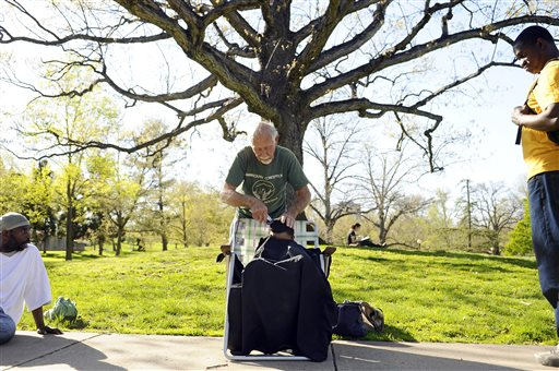 Colby Snow, 4, of Hartford, Conn., receives a haircut from Anthony Cymerys, 82, in Hartford's Bushnell Park, in this May 1, 2013, photo.