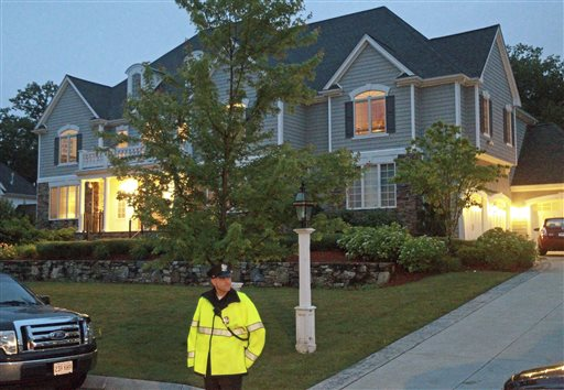 A police officer stands outside the home of New England Patriot's NFL football player Aaron Hernandez in North Attleborough, Mass., on Tuesday.