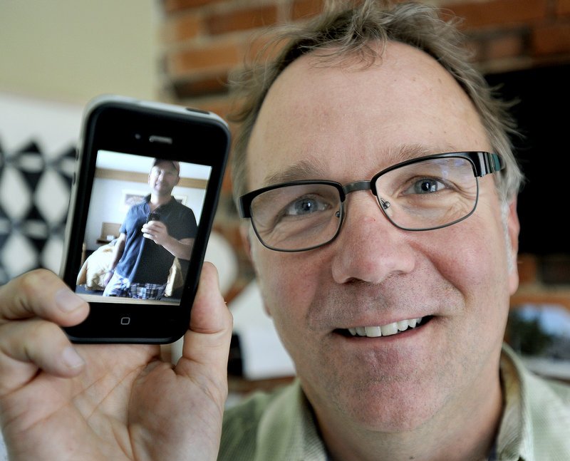Chris Kast, a brand strategist at The Brand Co. in Portland, is seen here with a photo of his husband Byron Bartlett on Wednesday, June 26, 2013. They were two of many local residents to celebrate the Supreme Court's ruling.