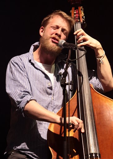 Ted Dwane, of the English folk rock band Mumford & Sons, performing at the Susquehanna Bank Center in Camden, N.J. in February. Dwane has a blood clot on his brain that will require surgery. The Grammy Award-winning folk-rock group has postponed concerts Tuesday, June 11, in Dallas, Wednesday June 12 in The Woodlands and Thursday, June 13 in New Orleans. A statement on its website said there are no plans to postpone or cancel any other appearances on the current tour. Mumford & Sons has a headlining gig Saturday at the Bonnaroo Music & Arts Festival in Manchester, Tenn. (Photo by Owen Sweeney/Invision/AP, file)