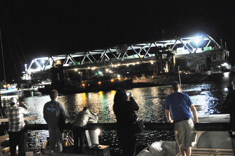 Spectators gathered as the final span of the new Memorial Bridge connecting New Hampshire and Maine floated down the Piscataqua River early Monday in Portsmouth, N.H. The bridge isn't open to traffic yet.
