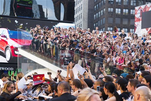 Actor Brad Pitt, lower left, signs autographs as he arrives to the