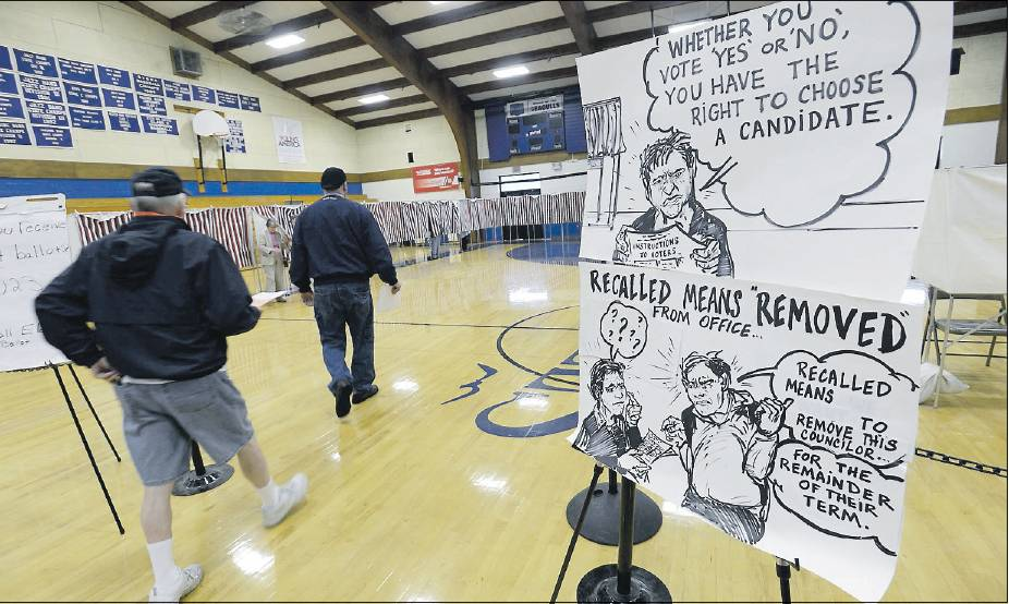 Residents make their way to the voting booths Tuesday at Old Orchard Beach High School, passing signs about councilor voting and explaining what a recall means. The signs were created by Channing Reeves, who lives in town.