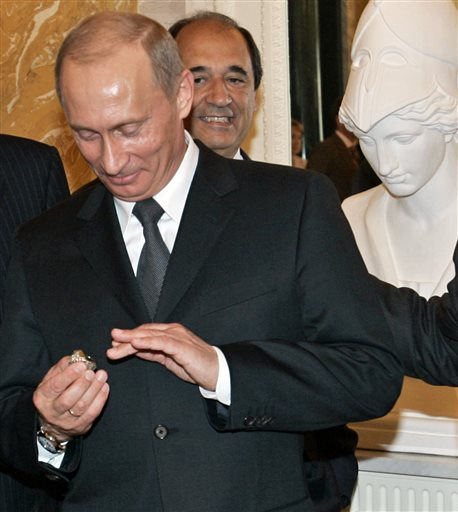 Russian President Vladimir Putin holds a 2005 Super Bowl ring belonging to New England Patriots owner Robert Kraft during a meeting outside St. Petersburg, Russia, in 2005. Kraft says Putin pocketed the ring, according to the New York Post; Putin says it was a gift.