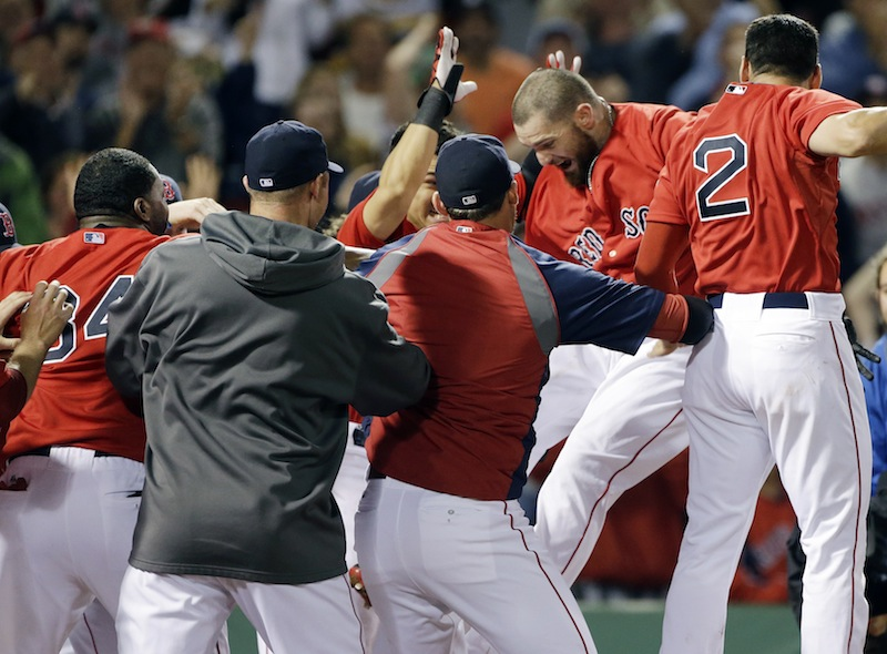 Boston Red Sox's Jonny Gomes jumps onto homeplate surrounded by teammates as he celebrates his two-RBI walk-off home run against the Tampa Bay Rays during the ninth inning of the second baseball game in a day-night doubleheader at Fenway Park in Boston, Tuesday, June 18, 2013. The Red Sox won 3-1. (AP Photo/Elise Amendola) Fenway Park