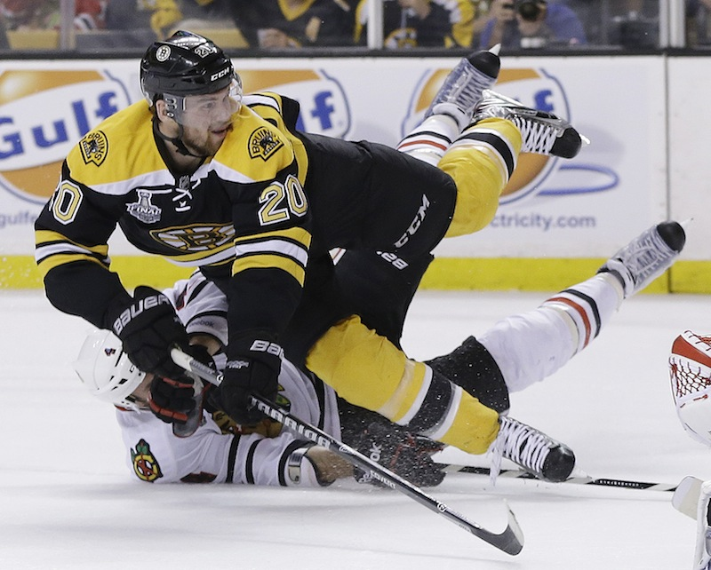 Chicago Blackhawks defenseman Niklas Hjalmarsson, bottom, of Sweden, takes down Boston Bruins left wing Daniel Paille (20) during the second period in Game 3 of the NHL hockey Stanley Cup Finals in Boston, Monday, June 17, 2013. The Bruins scored the game's second goal on the power play that followed. (AP Photo/Elise Amendola) TD Garden