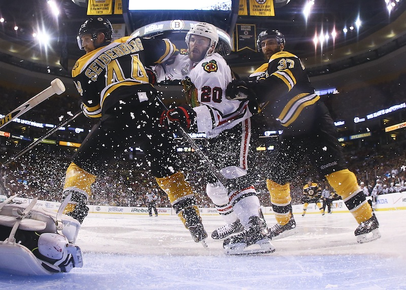Boston Bruins defenseman Dennis Seidenberg (44), of Germany, and center Patrice Bergeron (37) check Chicago Blackhawks left wing Brandon Saad, center, in front of the goal during the second period in Game 6 of the NHL hockey Stanley Cup Finals Monday, June 24, 2013, in Boston. (AP Photo/Harry How, Pool) TD Garden