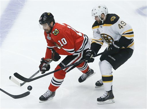 Chicago Blackhawks center Patrick Sharp fights for the puck against Boston Bruins center Rich Peverley in the first period during Game 2 of the NHL hockey Stanley Cup Finals Saturday in Chicago.