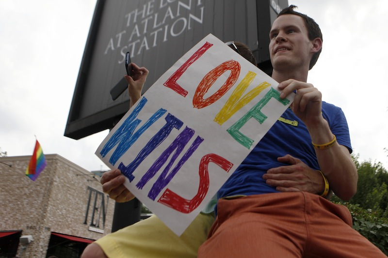 Daniel Hicks sits on a pillar with his boyfriend to watch the local crowd celebrate the U.S. Supreme Court's rulings on two landmark gay rights cases surrounding same-sex marriage on the corner of Piedmont Ave. and Tenth Street in Midtown, Wednesday, June 26, 2013, in Atlanta. (AP Photo/Jaime Henry-White)