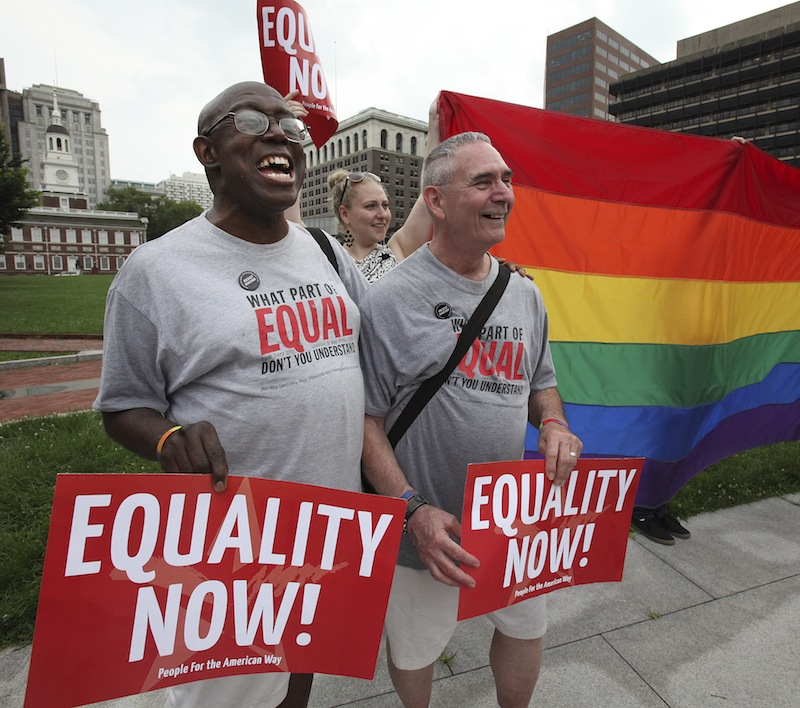 Stevie Martin-Chester, left, and his husband of 20 years, Arthur Martin-Chester, from Norristown, attend a rally in support of Wednesday's landmark Supreme Court rulings on gay marriage Wednesday, June 26, 2013, at Independence Mall in Philadelphia. (AP Photo/Philadelphia Daily News, Steven M. Falk) 304d50305756384c;696e717763