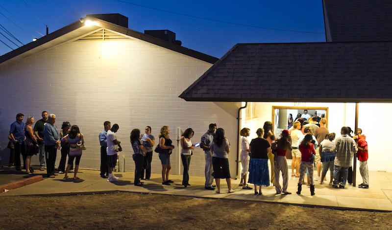 People wait in line to vote at polling place located in a church in Phoenix in this Nov. 6, 2012, file photo. The Supreme Court ruled Monday, June 17, 2013, that states cannot on their own require would-be voters to prove they are U.S. citizens before using a federal registration system designed to make signing up easier. The justices voted 7-2 to throw out Arizona's voter-approved requirement that prospective voters document their U.S. citizenship in order to use a registration form produced under the federal