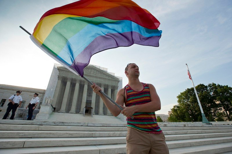 Gay rights advocate Vin Testa waves a rainbow flag in front of the Supreme Court at sun up in Washington, Wednesday, June 26, 2013. In two separate and significant victories for gay rights, the Supreme Court struck down a provision of a federal law denying federal benefits to married gay couples and cleared the way for the resumption of same-sex marriage in California. (AP Photo/J. Scott Applewhite)
