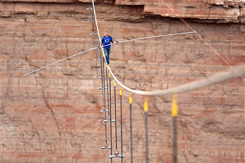 Aerialist Nik Wallenda walks a 2-inch-thick steel cable taking him a quarter mile over the Little Colorado River Gorge, Ariz. The daredevil successfully traversed the tightrope strung 1,500 feet above the chasm near the Grand Canyon in just more than 22 minutes, pausing and crouching twice as winds whipped around him and the cable swayed.