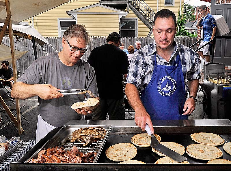 Bill Doukas, left, and Tim Morrell make the very popular gyros, about 200 an hour according to Doukas, for visitors Saturday at the Greek Food Festival at the Holy Trinity Greek Orthodox Church in Portland.