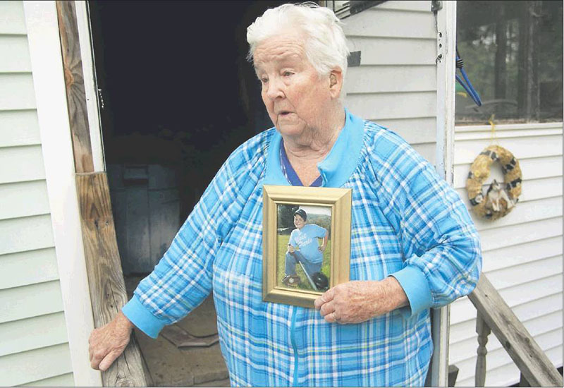 Eleanor Paine of West Paris holds a picture of her grandson, James Reynolds, when he was younger as she talks to a reporter Monday outside her home. She said that when Reynolds' mother was at work, her son often spent time at Paine's house.